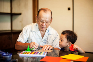 Japanese man and little boy sitting at a table, making Origami animals using brightly coloured paperの写真素材 [FYI02264876]