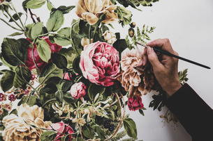 Close up of artist working on painting of pink tea roses, leaves, berries and other flowers.の写真素材 [FYI02264879]