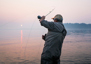 Senior Caucasian male fly fishing for salmon and sea run cutthroat trout off the coastの写真素材 [FYI02264884]