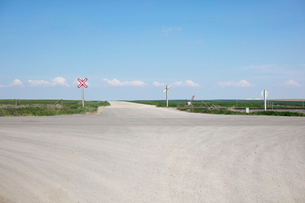 Railroad crossing along rural road and farmland,の写真素材 [FYI02264888]