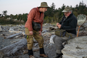 A male fly fisherman watches his guide work putting on a new fly to try for salmon or trout at a salの写真素材 [FYI02264898]