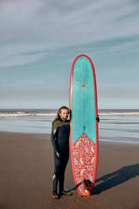 Portrait of a man holding a decorated surf board on a sandy beachの写真素材 [FYI02264899]