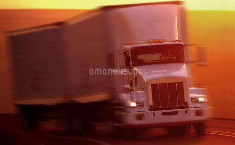 A truck tractor pulling a double load of trailers around a corner on a highway, sunsetの写真素材 [FYI02264905]