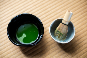 Tea ceremony utensils including bowl of green Matcha tea and bamboo whisk.の写真素材 [FYI02264908]