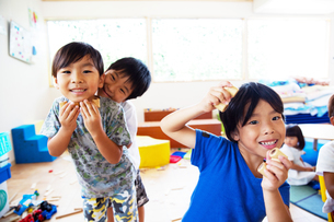 Three young children in a Japanese preschool, looking at camera and pulling faces, smiling.の写真素材 [FYI02264917]
