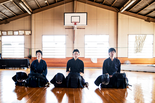 Female and two male Japanese Kendo fighters kneeling on wooden floor, meditating.の写真素材 [FYI02264944]
