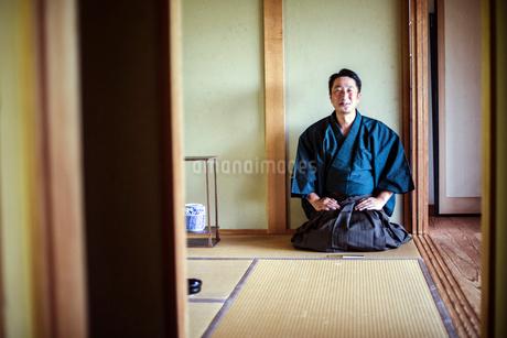 Japanese man wearing kimono kneeling on floor, on a tatami mat during tea ceremony.の写真素材 [FYI02264951]