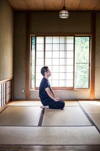 Japanese man kneeling on tatami mat in traditional Japanese house.の写真素材 [FYI02264952]
