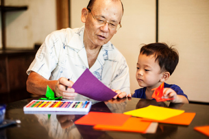 Japanese man and little boy sitting at a table, making Origami animals using brightly coloured paperの写真素材 [FYI02264954]