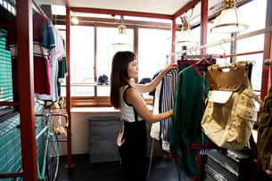 Japanese saleswoman standing in clothing store, arranging clothes on a rail.の写真素材 [FYI02264963]