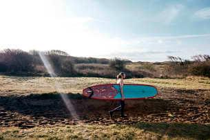 Man holding surf board walking along sandy path towards the seaの写真素材 [FYI02264966]