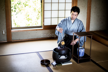 Traditional Japanese Tea Ceremony, man wearing kimono sitting on tatami mat using a Hishaku, a bamboの写真素材 [FYI02264974]