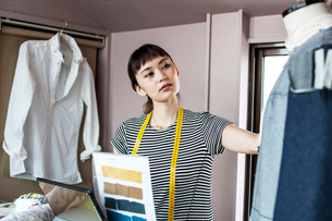Japanese female fashion designer working in her studio, looking at garment on dressmaker's model.の写真素材 [FYI02264978]