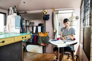 Japanese female fashion designer sitting at desk, working in her studio.の写真素材 [FYI02264980]