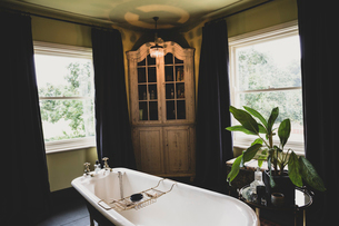Interior view of bathroom with wooden corner cabinet  between sash windows, roll top bath with brassの写真素材 [FYI02264991]