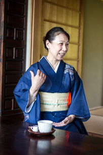 Smiling Japanese woman wearing blue kimono sitting on floor in traditional Japanese house.の写真素材 [FYI02264996]