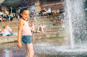 Smiling girl playing in public fountain in summerの写真素材 [FYI02265012]