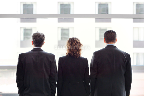 Rear view of group of three business people looking out the window of a conference centre lobby.の写真素材 [FYI02265014]