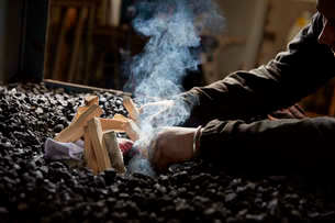 A metal worker lighting a furnace fire using wooden sticks and paper on top of a heap of coal.の写真素材 [FYI02265015]