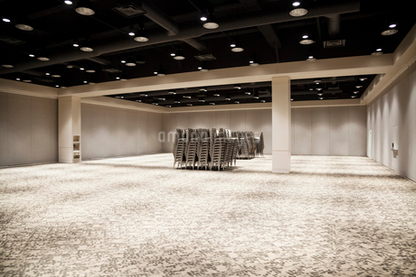 Stacked chairs in an empty convention centre meeting room.の写真素材 [FYI02265018]