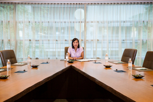 Asian businesswoman at the head of a conference room table.の写真素材 [FYI02265019]