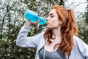 Young woman with long red hair wearing sports kit, exercising outdoors, drinking from water bottle.の写真素材 [FYI02265022]