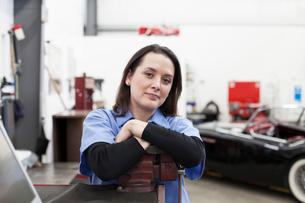 A portrait of a Caucasian female mechanic in a car repair shop.の写真素材 [FYI02265023]