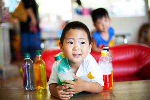 Young boy holding bottle with green liquid in a Japanese preschool.の写真素材 [FYI02265036]