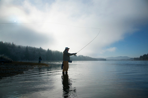 Silhouette of fisherman fly fishing for salmon and sea run cutthroat troutの写真素材 [FYI02265051]