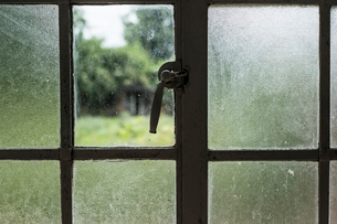 Close up of window with broken pane, view of overgrown garden with shed in the distance.の写真素材 [FYI02265053]