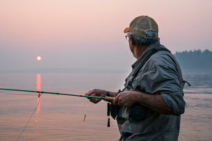 Senior Caucasian male fly fishing for salmon and sea run cutthroat trout off the coastの写真素材 [FYI02265067]