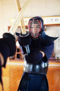 Two Japanese Kendo fighters wearing Kendo masks practicing with wood sword in gym.の写真素材 [FYI02265068]