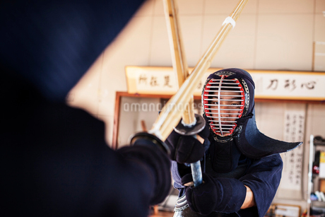 Two Japanese Kendo fighters wearing Kendo masks practicing with wood sword in gym.の写真素材 [FYI02265073]