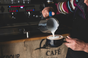 Close up of barista pouring milk from jug into cappuccino mug, creating foam pattern.の写真素材 [FYI02265074]