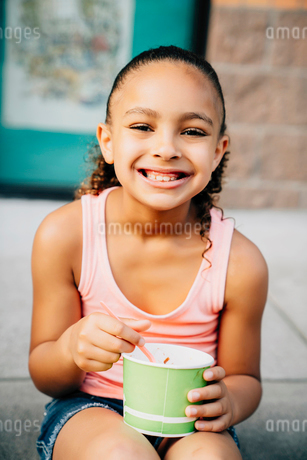 Smiling girl sitting on steps eating ice creamの写真素材 [FYI02265083]