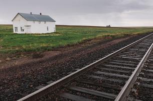Abandoned farmhouse on prairie, train tracks in foreground, Saskatchewan, Canada.の写真素材 [FYI02265087]