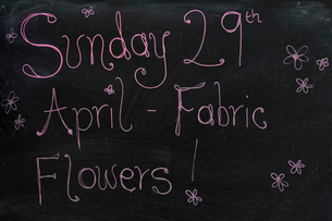 Close up of blackboard with handwriting advertising fabric flower workshop.の写真素材 [FYI02265092]