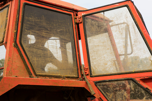 Close up of farmer sitting in a red tractor with dirty windows.の写真素材 [FYI02265094]