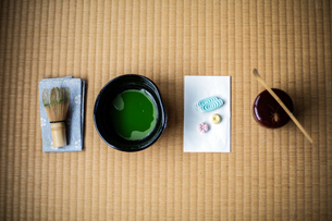 Tea ceremony utensils including bowl of green Matcha tea, a bamboo whisk and Wagashi sweets.の写真素材 [FYI02265095]