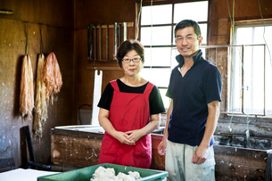 Japanese woman and man standing in a Washi workshop by a vat of pulp, basic plant based ingredientsの写真素材 [FYI02265101]