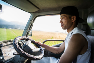 Portrait of Japanese farmer sitting in his tractor.の写真素材 [FYI02265105]