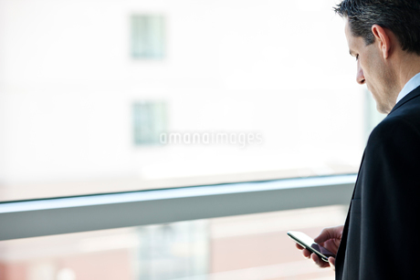 Caucasian businessman checking his cell phone in a conference centre lobby.の写真素材 [FYI02265107]