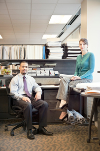 Portrait of a young Black businessman and Caucasian businesswoman in an office cubicle.の写真素材 [FYI02265110]