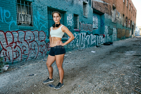 Female athlete standing on street in front of blue building covered in graffiti, looking at camera.の写真素材 [FYI02265130]