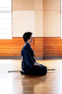 Side view of female Japanese Kendo fighter kneeling on wooden floor.の写真素材 [FYI02265134]
