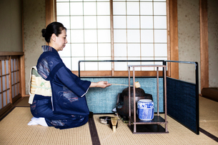 Japanese woman wearing traditional bright blue kimono with cream coloured obi kneeling on floor, usiの写真素材 [FYI02265144]
