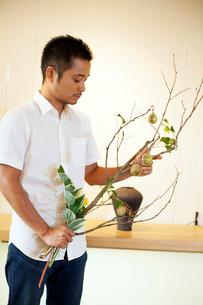 Japanese man working in a flower gallery, working on Ikebana arrangement.の写真素材 [FYI02265145]