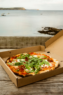 A takeaway pizza in a brown box.の写真素材 [FYI02265148]