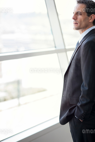 Closeup of a Caucasian businessman looking out the widow of a conference centre lobby.の写真素材 [FYI02265160]
