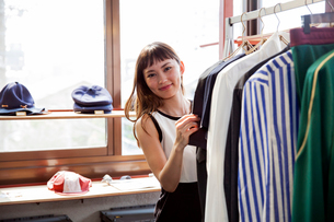Smiling Japanese saleswoman standing in clothing store, looking at shirt.の写真素材 [FYI02265164]